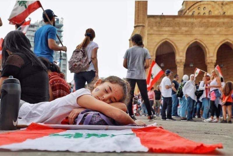 A young girl rests on a Lebanese flag at a protest in Beirut in 2019.