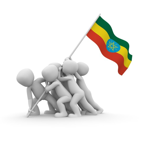 A huddle of featureless white figures lifts the Ethiopian flag.