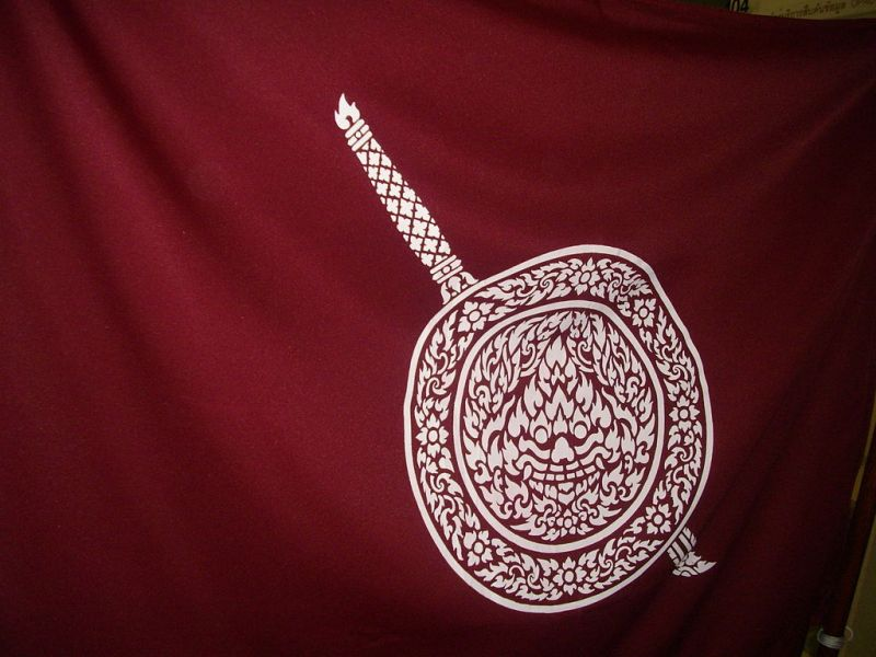 The Royal Thai Police flag, maroon with a white seal depicting a sword and carved shield.
