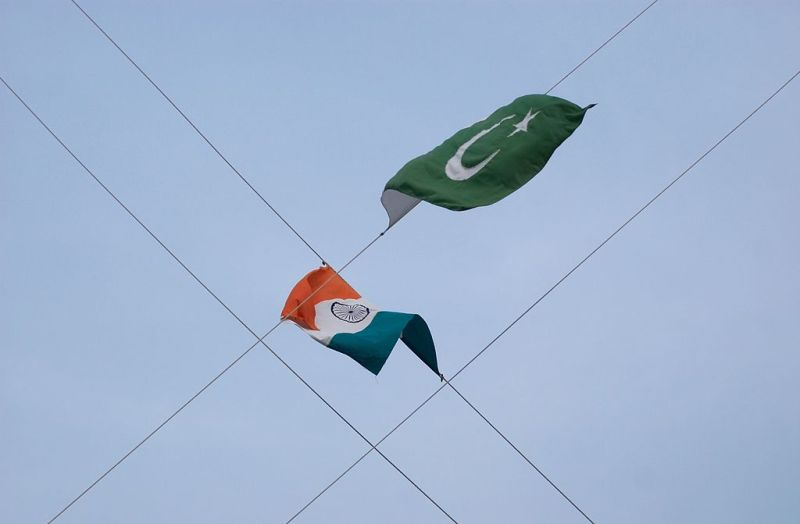 India and Pakistan's flags hang on four crossed wires at the border between the two countries.