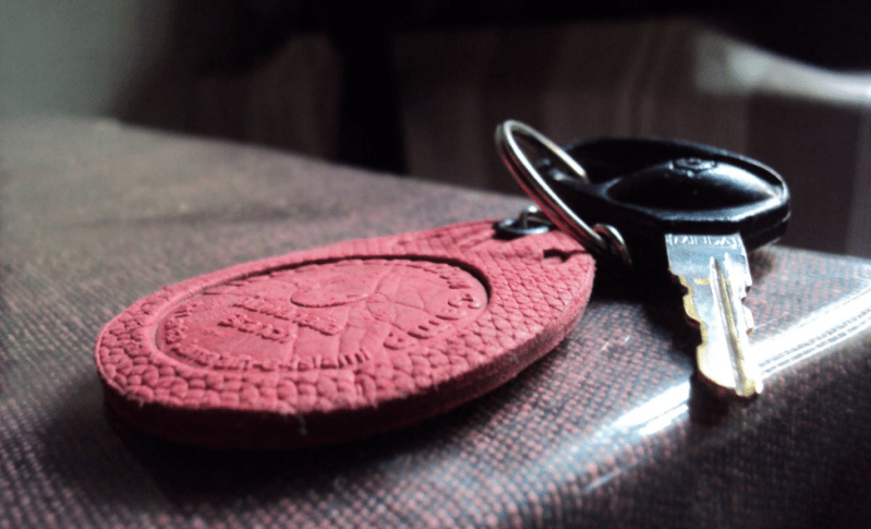 A key with a red tag lies on a cushion. The tag is in focus.