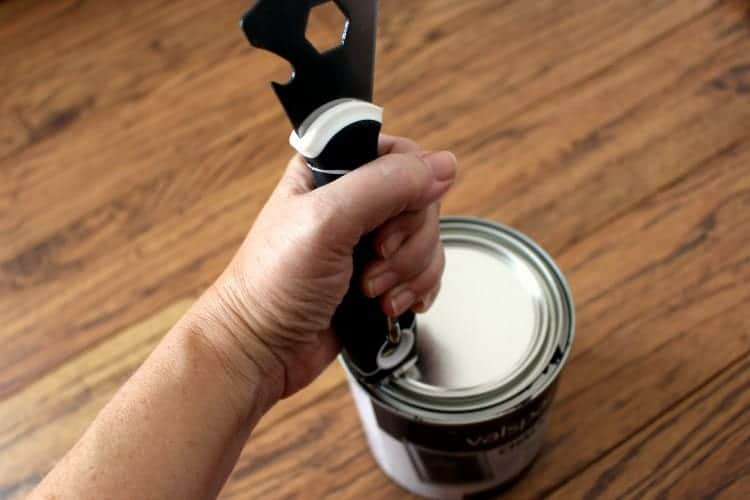 Using a painter's tool to hammer the lid back onto a can of paint.