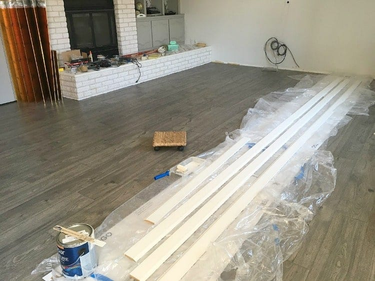 Baseboards painted white and waiting to be installed