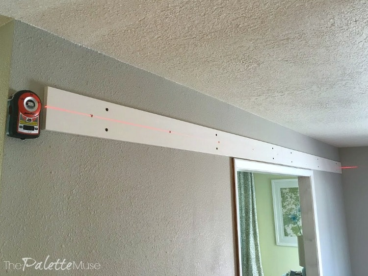 Using a laser level to install barn doors.