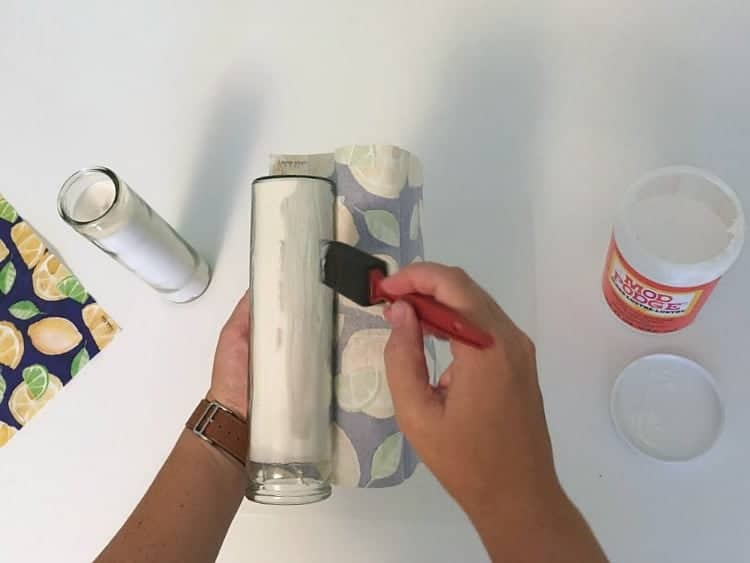 Adding ModPodge glue to a glass candle holder to decorate it with a napkin.