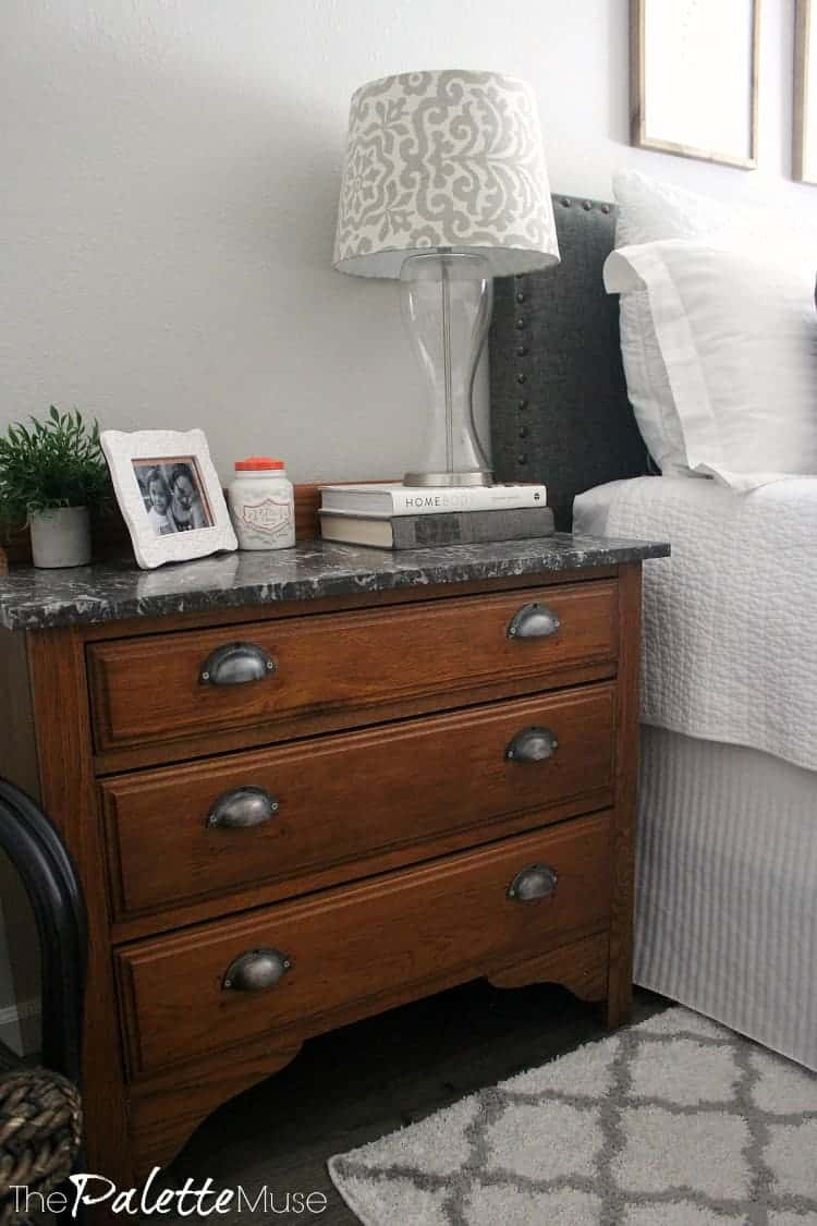 Wood dresser with gray marble top serves as nightstand next to the bed.