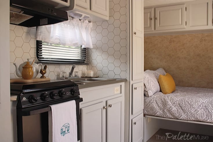 Bright camper interior with light gray cabinets and white accent pieces.