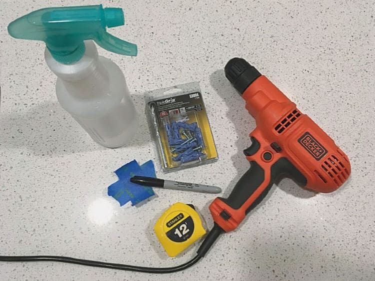 Supplies for drilling into a tile backsplash to hang mirrors. You'll need a drill, a masonry bit and masonry anchors, a spray bottle with water, and tools for marking the spot.