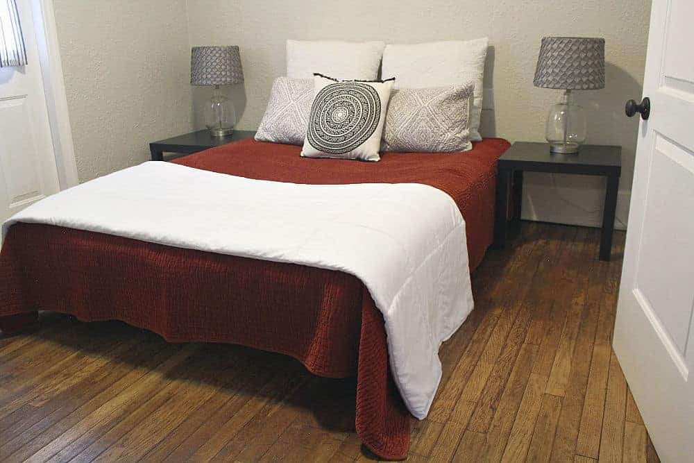 Queen bed with white covers and warm hardwood floors.