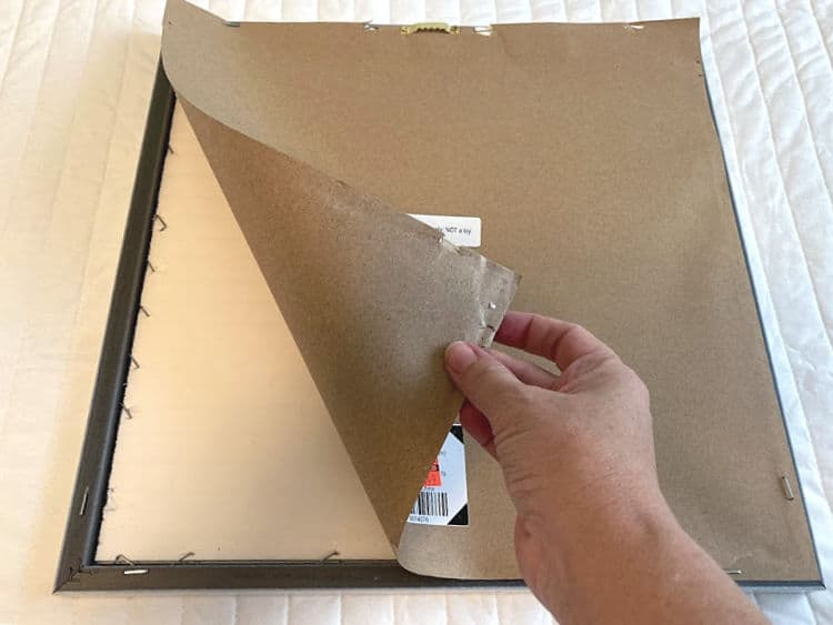Peeling the paper backing off a framed print