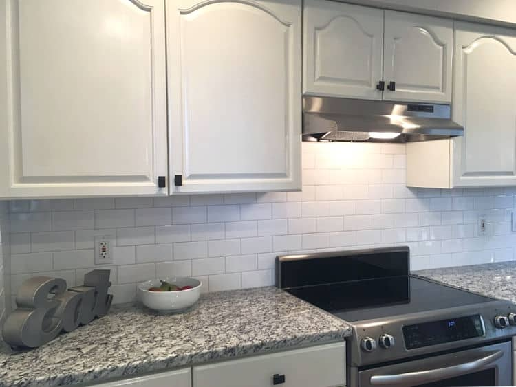 White kitchen cabinets with gray granite countertop