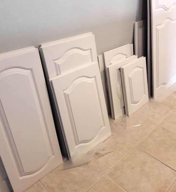 White painted cabinet doors leaning against the wall to dry