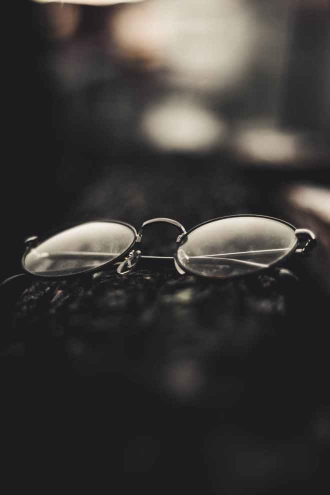 grayscale photography of folded eyeglasses