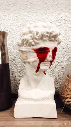 bust sculpture with bandaged eyes and blood tears