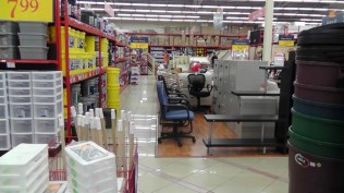 On the left is the back of the paint department with the 5 gallon buckets. In the center area is furniture, mainly desks, chairs, filing cabinets, and some tables.