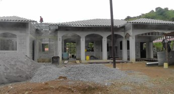 This is a house under construction in our neighborhood. You can see the block construction. They have removed the forms used to apply concrete to the curved window frames, and they are starting to install the roof which is a decorative, reflective tin slightly different from the basic tin that is often used.