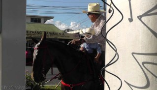 The water hose at the gas station was used frequently to hose down horses and give them a drink. It was a hot day.