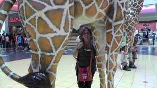 Holly can almost hide under a giraffe