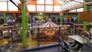There is a huge two story food court with a merry go round in the middle