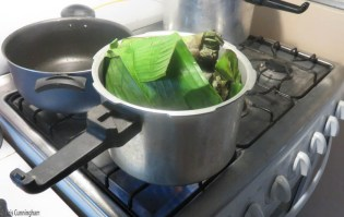 The bundle of plantain leaves boiling on the stove.