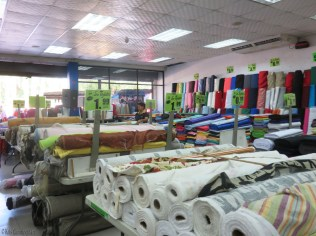 This is from inside the store (shhh). There is a bit of upholstery fabric in the foreground, and then clothing and other fabric in the background. The walls are also lined with bolts of fabrics.