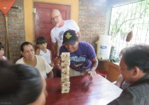 The jenga game continues. The doctor's mom is across the table with the glasses, and that is one of his sons behind her. The birthday guy is in the white t-shirt.