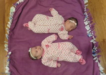 Two babies, one awake and one asleep