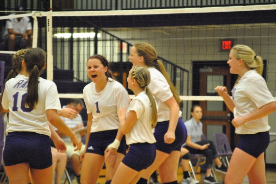 Varsity volleyball team celebrates after scoring a point on Christian Academy.