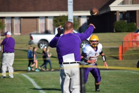 Coach Balsmeyer helps Junior football player Jeramy Hoffman warm up by throwing a football with him.