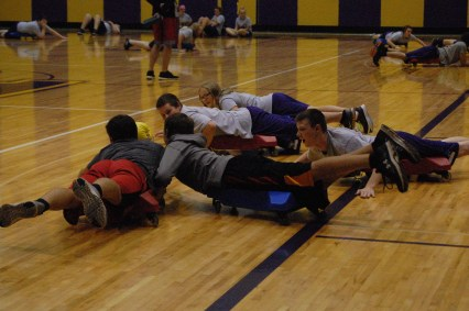 A group of boys trying to catch the ball in a game during gym class.