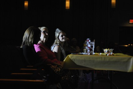The judges are seated and watch the girls on the stage.