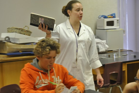 The eighth grade science teacher gives directions to the students on how to do their experiment.