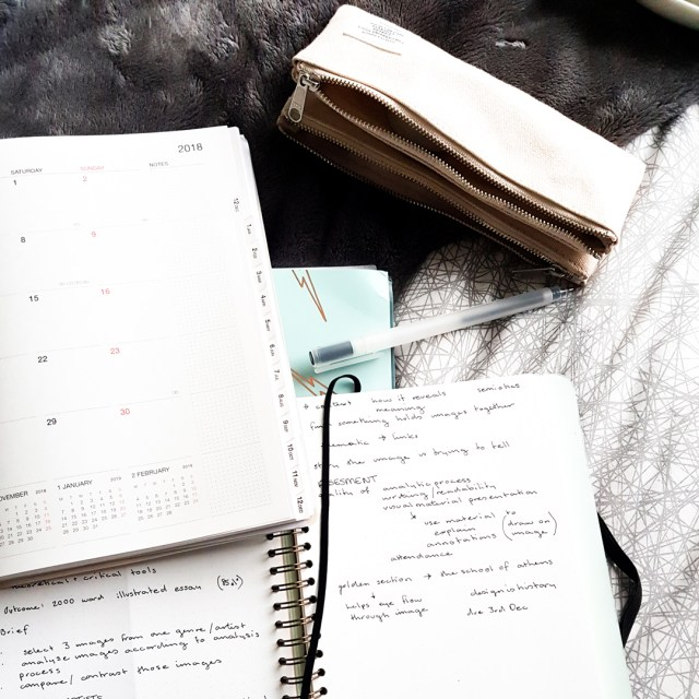 image shows lecture notes in notebook with academic planner and pencil case