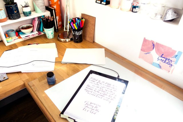 Image shows desktop with calligraphy practice on sheets of paper.