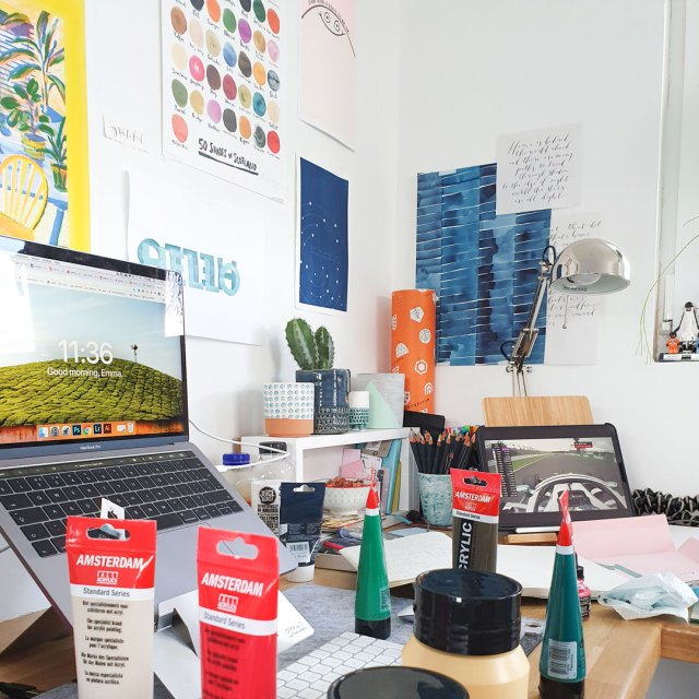 Workspace covered in tubes of paint.