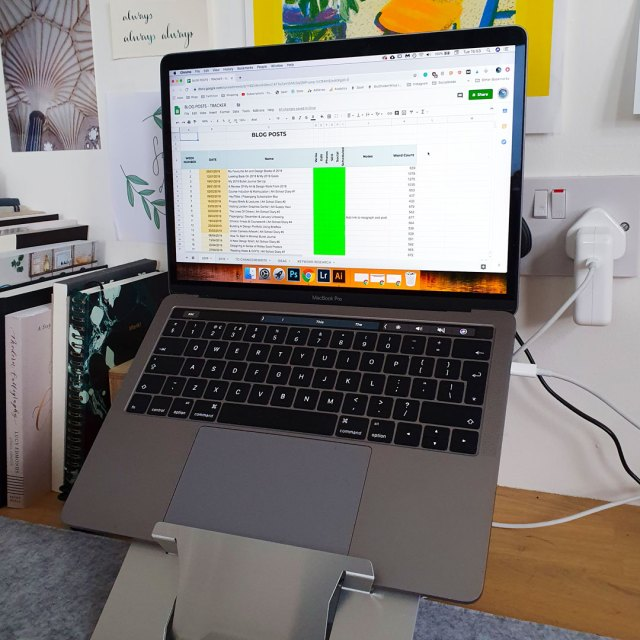 Image shows laptop sitting on desk with spreadsheet shown on screen.