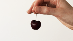 A hand holding a cherry.