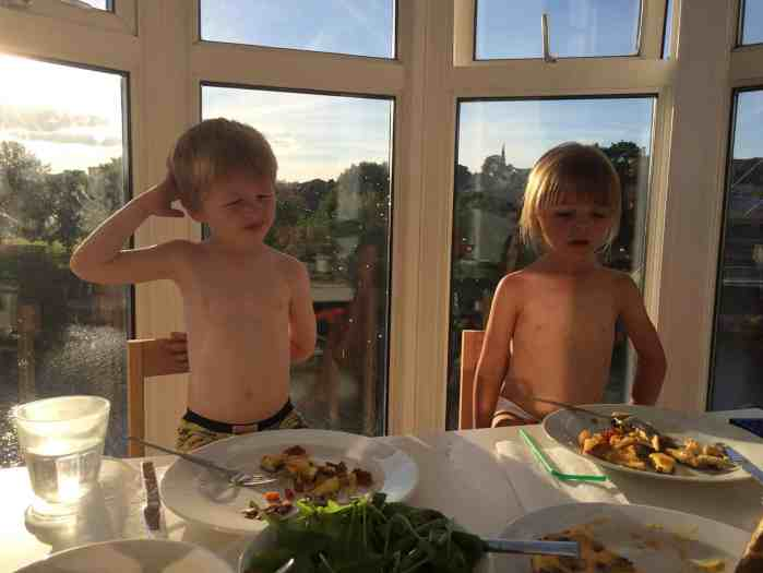 Two children eating dinner in the sunshine on a playdate