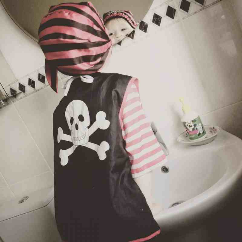 Photo of a little boy from behind wearing a skull and crossbones top, pirate hat and brushing his teeth.