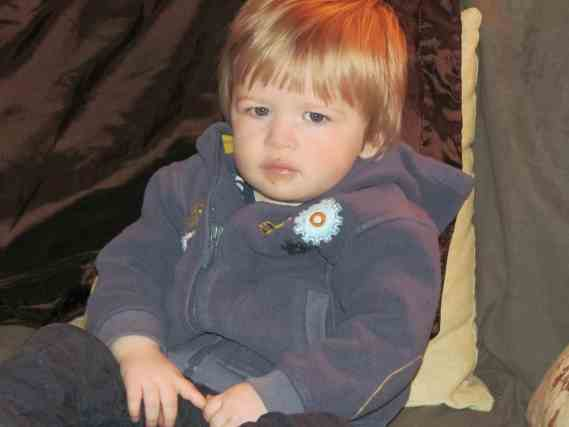 Little boy about two with long blonde hair frowning at the camera