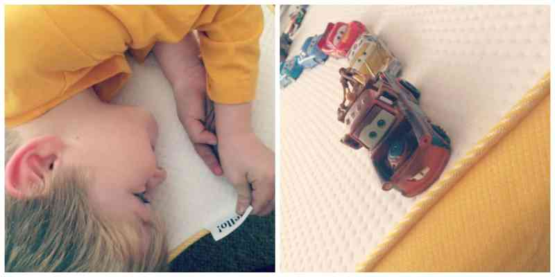 Little boy playing with a row of cars on a white and yellow mattress