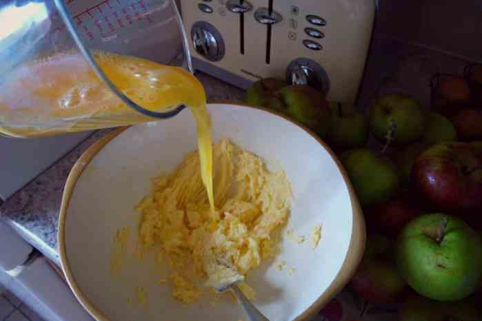 yellow egg being poured into a white bowl