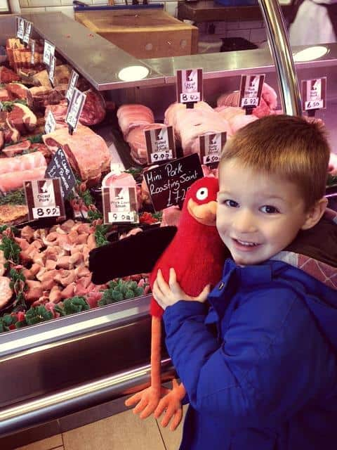 Little boy at butchers in a blue coat