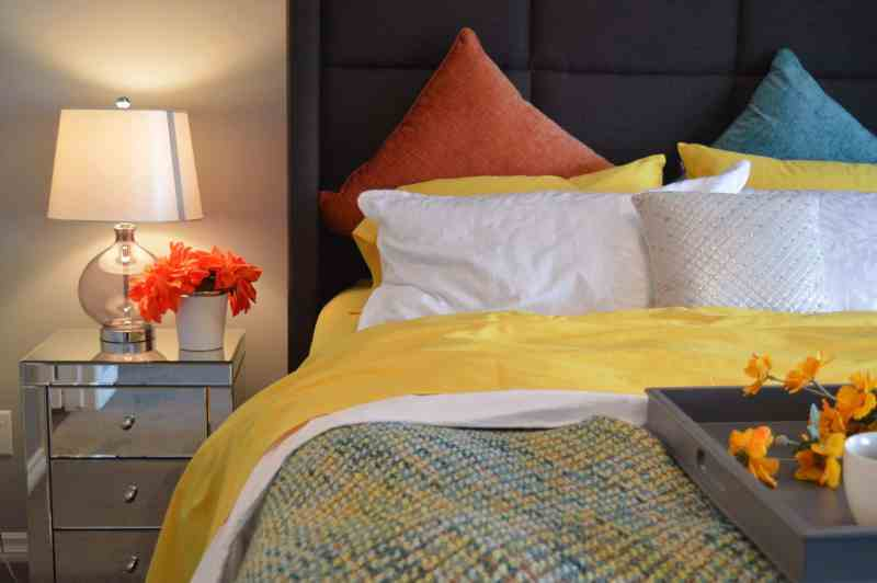 bed with white yellow and orange cushions