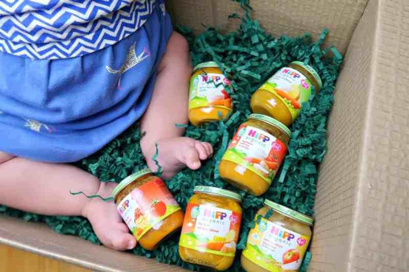 HiPP babyfood jars in box by babies feet