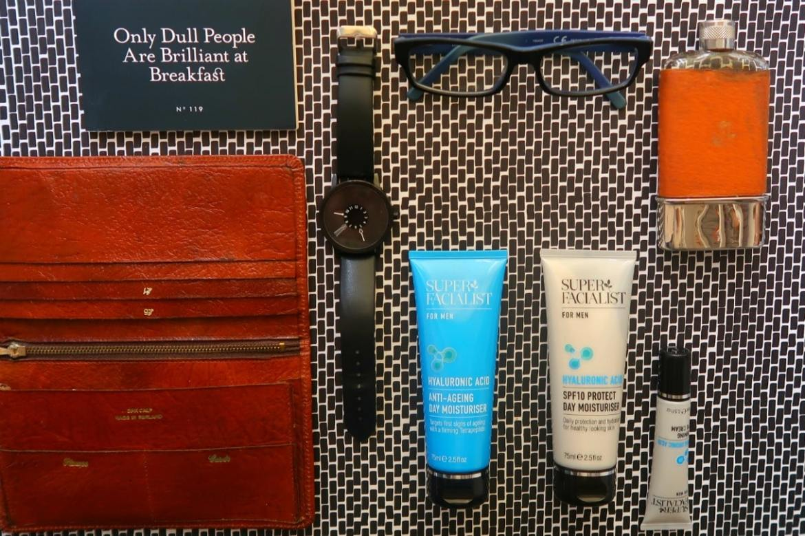 Fathers Day gift guide flatlay, black watch, leather wallet, blue glasses and two matching skincare bottles.
