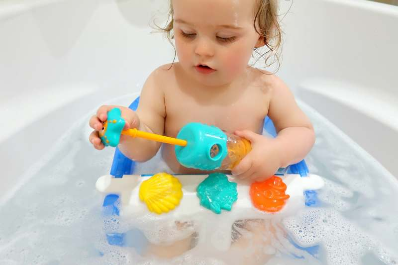 Picture of a baby in a bath with a blue and yellow Hape water squirter