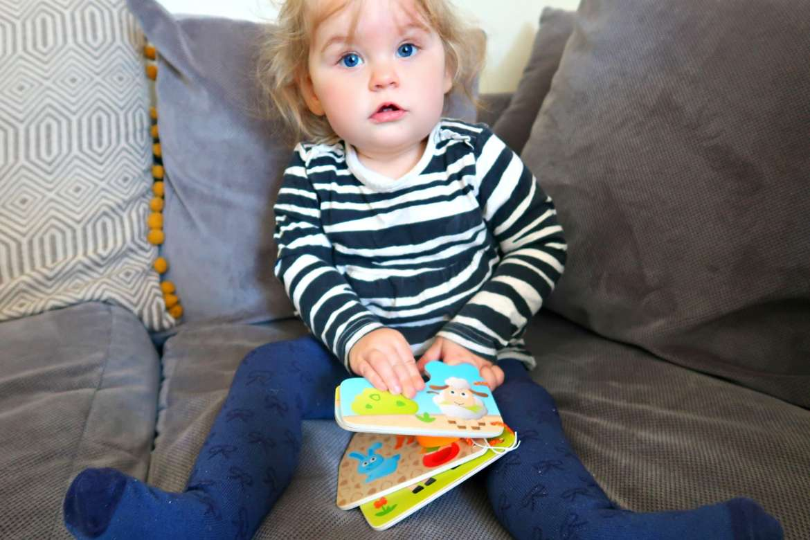 Baby girl in blue tights on the sofa reading wooden Hape book with farm animals on