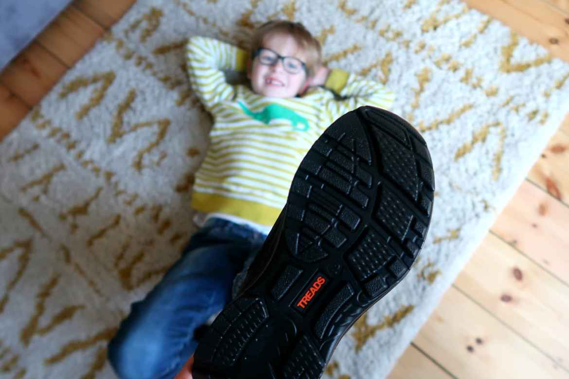 Blong boy with foot in the air wearing black shoe with Treads written in orange