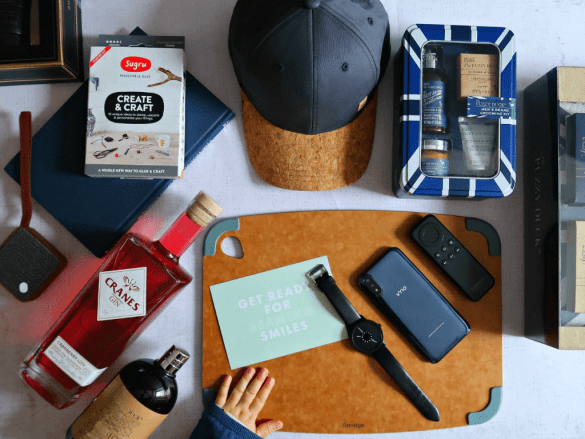 Father's day gifts flat pay, blue cap, blue mobile, black watch, brown speaker and brown chopping board.